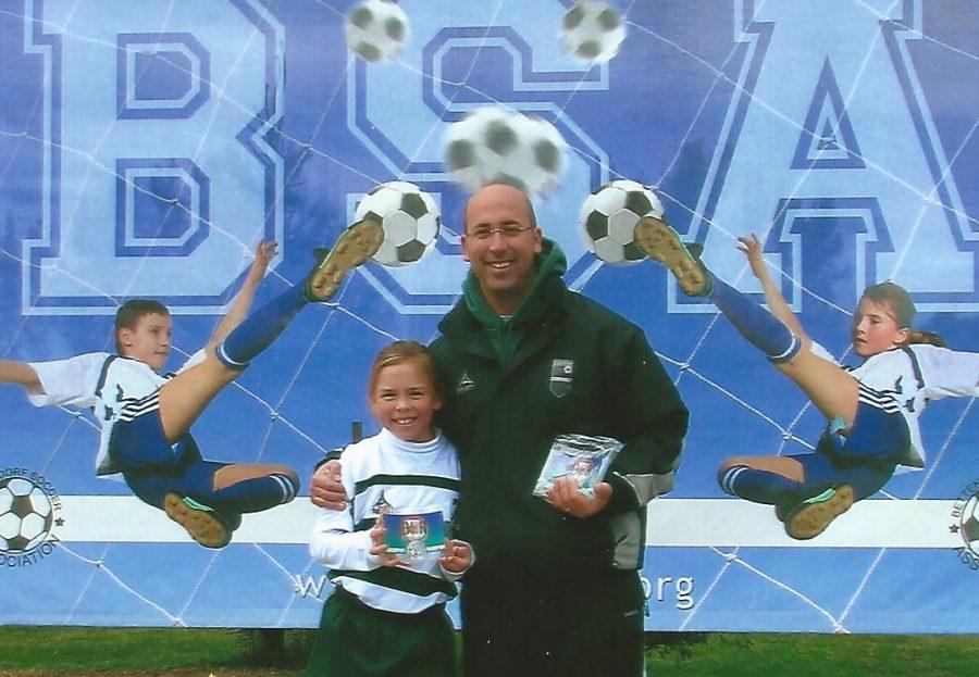 Junior Janessa Klein flaunts her participation trophy next to her dad as a child. Barb Klein Photo.