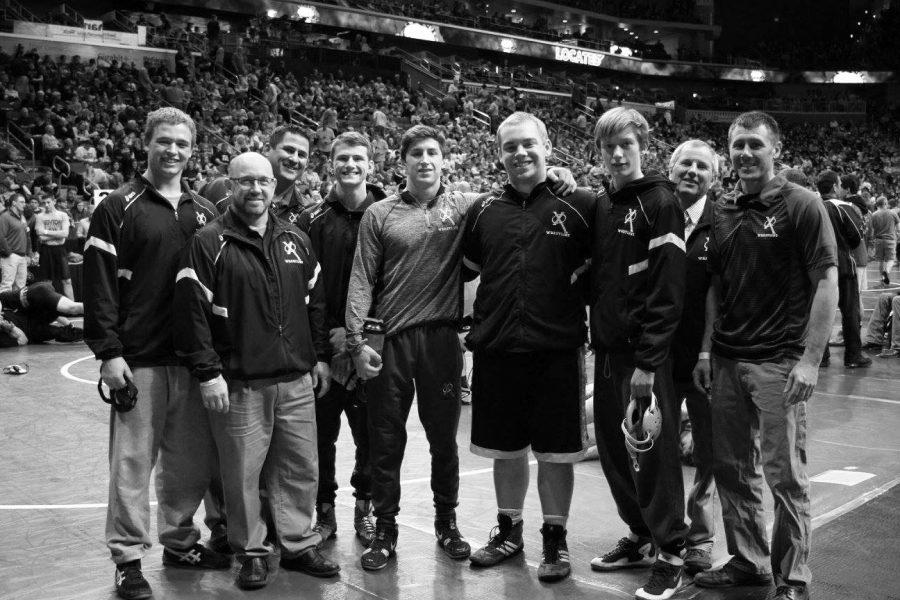 Above: Xavier wrestling team members and coaches pose for a photo at the Wells Fargo Arena in Des Moines.