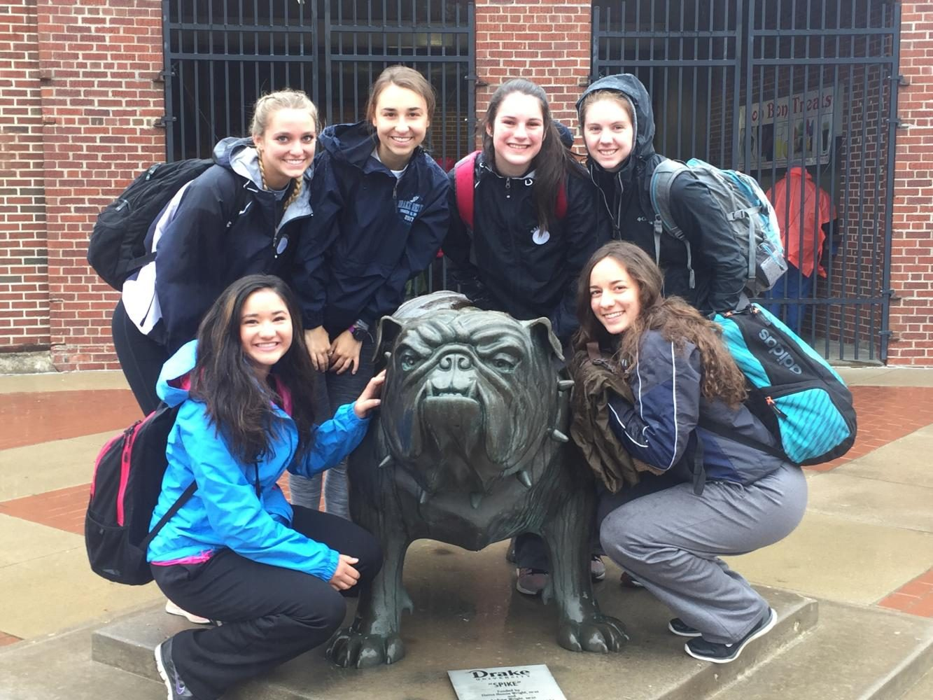 """Members of the girls' track team pose with """"Spike the bulldog"""" outside of the Drake stadium. Tallett Photo."""