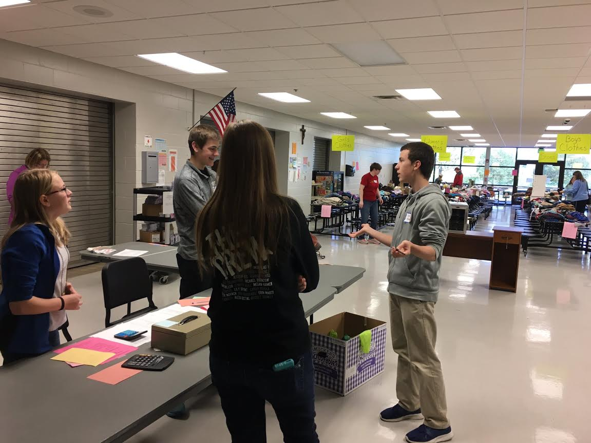 Students direct a customer at the garage sale to what she is looking for. Ms. Kelli Swehla Photo.