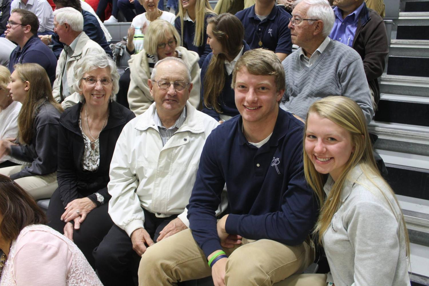 Devin Lansing (X17) and Rilee Lansing (X20) sit with their grandparents before Mass. Mr. Nick Ireland Photo.
