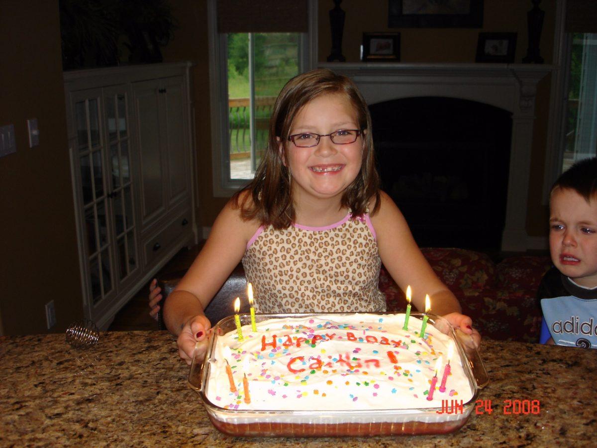Senior Caitlin Kramer holds her birthday cake while wearing glasses. Lynn Kramer Photo.
