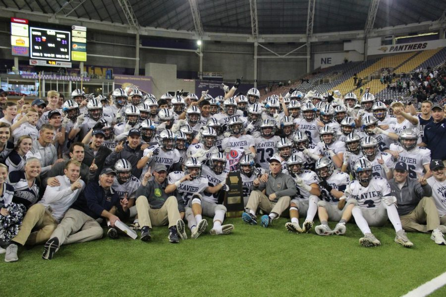 Football players, cheerleaders, and coaches pose with the state championship trophy in the UNI Dome after beating Pella 31-13 on Thursday, November 16. Camryn McPherson Photo.