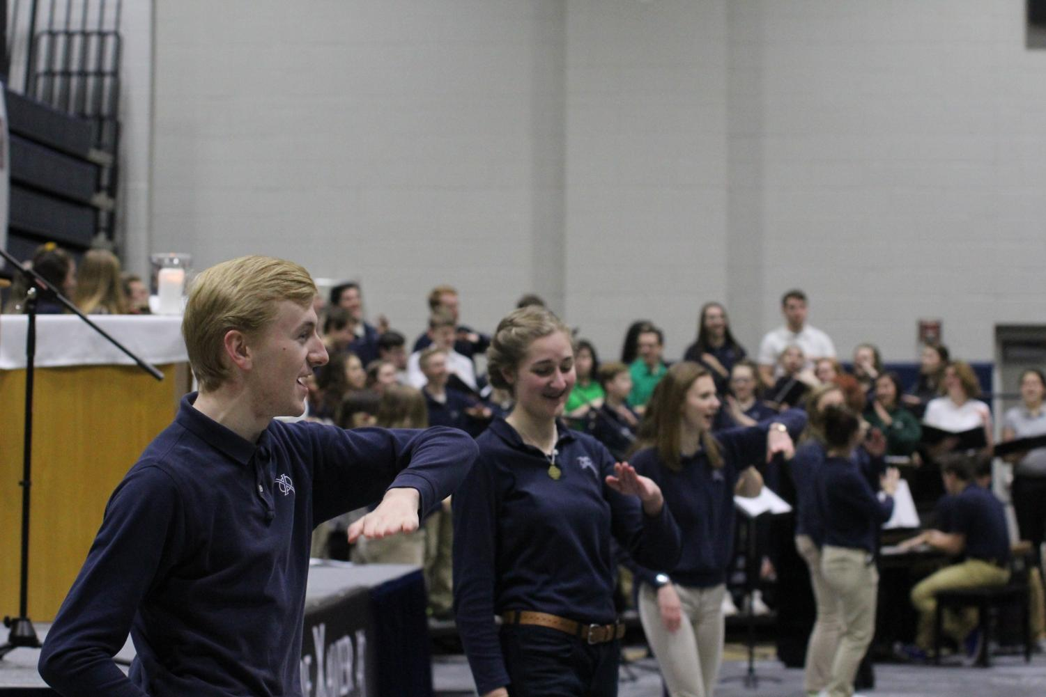 Senior Caleb Burken and junior Chloe Kepros lead middle school students in song at the Catholic Schools Week Mass. Camryn McPherson Photo.