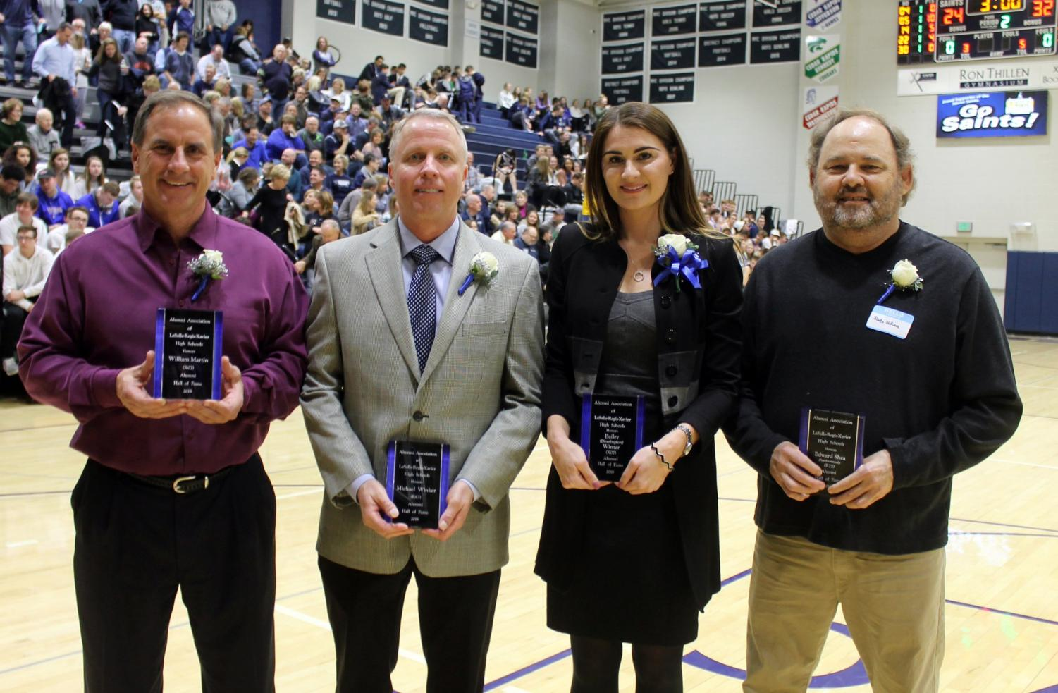 The new Hall of Fame inductees are honored at halftime of the Xavier varsity boys' basketball game. Nick Ireland Photo.