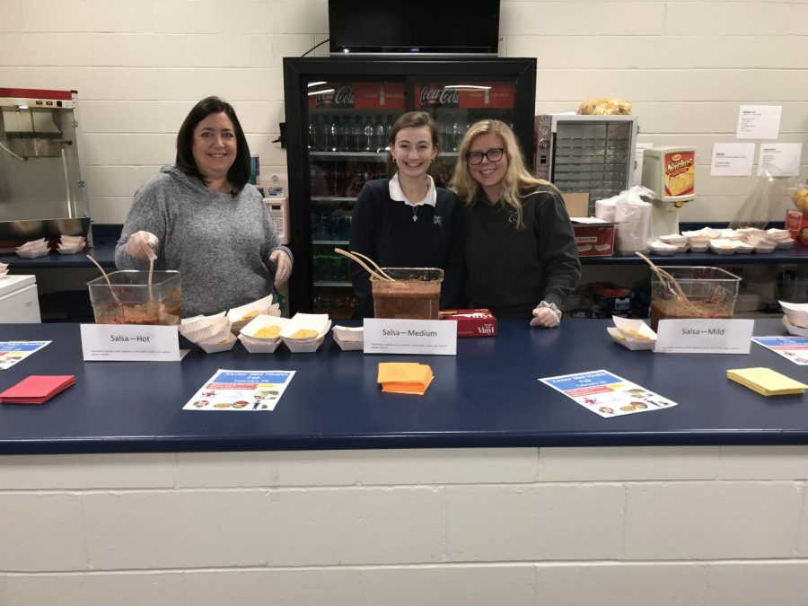Kris Naeve, Sydney Harris, and Claire Delaney serve fresh salsa to students during  lunch. Ellie McDermott Photo.