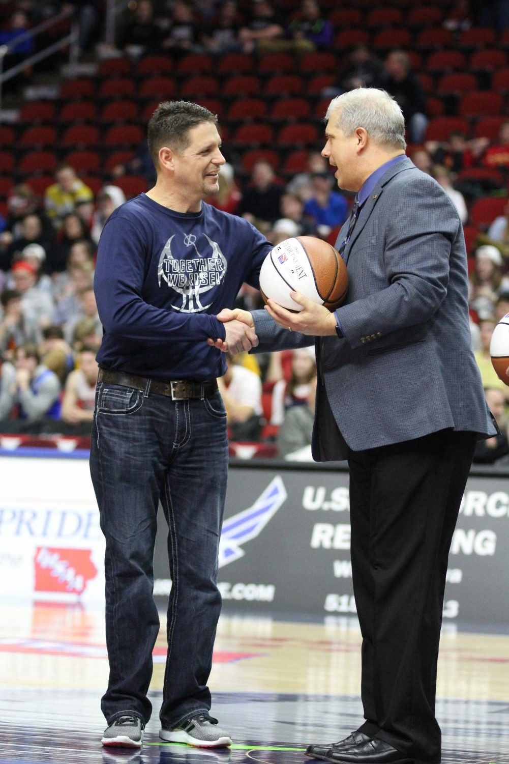 Kevin Lux, father of Nate (X15), Gabe (X18), and Jack (X21),  receives the Fan of the Game award and a commemorating basketball at the Wells Fargo Arena before the state quarterfinal game against Marion. Camryn McPherson Photo.