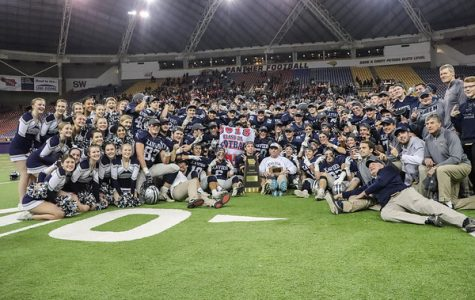The varsity football team displays their championship trophy and banner after their game against Western Dubuque. The Saints defeated the Bobcats 34-20.